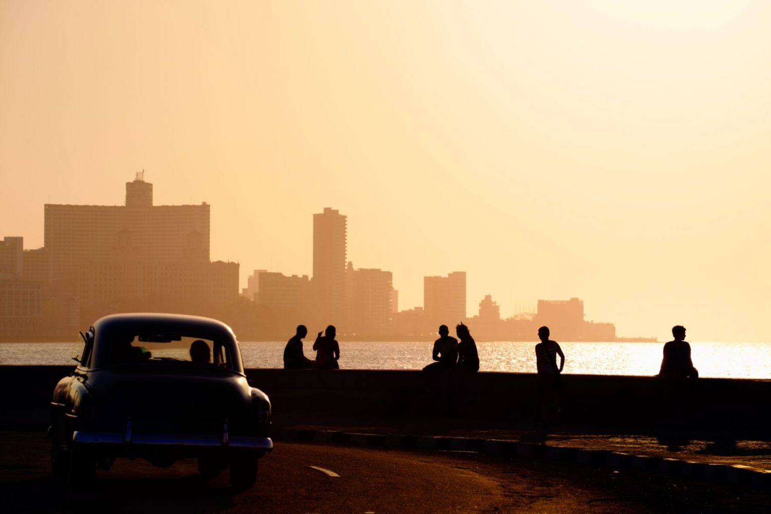 Skyline in La Habana, Cuba, at sunset, with vintage cars on the street and people sitting on the Malecon